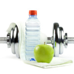 Metal dumbell with green apple, bottle of water and towel.